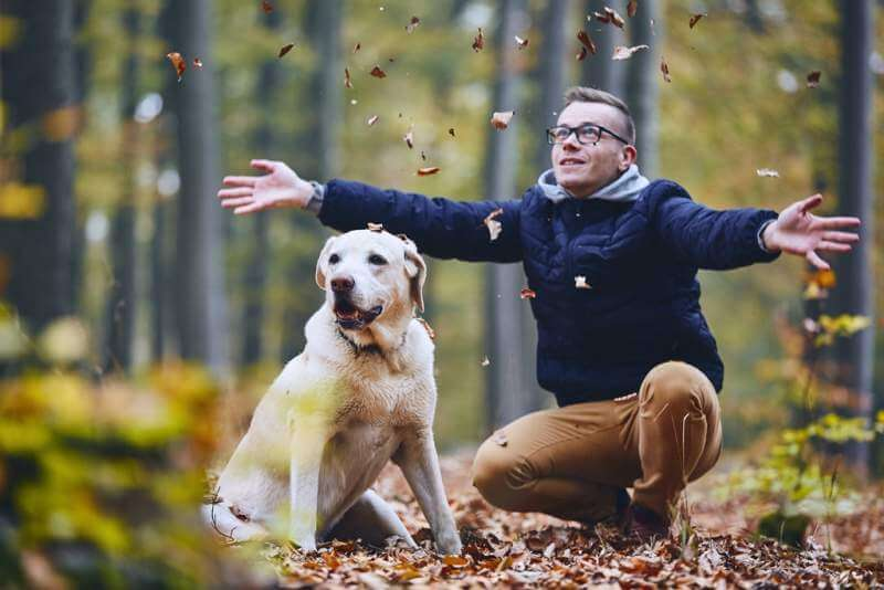 man-with-dog-in-autumn-forest